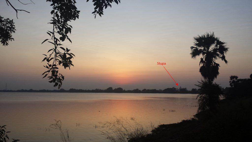 Solnedgang ud over sø med en enkelt stupa i baggrunden (med pil)