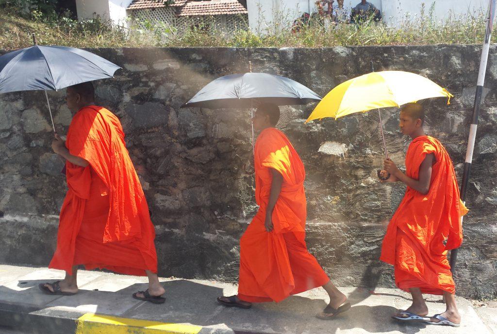 Tre munke med paraplyer